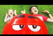 见 学习颜色与滑稽M&M`s糖果有趣的婴儿与巨型M&MS甜点有趣的婴儿恶作剧